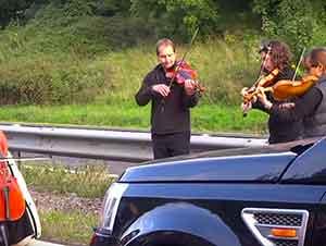 Un grupo de personas tocan música clásica en medio de un embotellamiento.