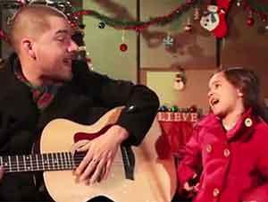 Padre e hija cantan Feliz Navidad juntos.