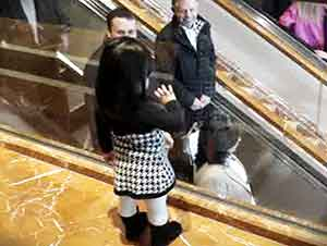 Pequeña se despide de la gente en el centro comercial.