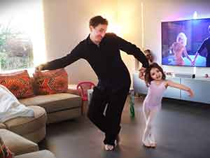 Padre e hija bailan de manera muy simpática.