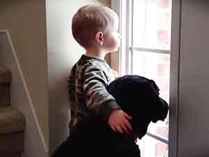 Un tierno niño acompaña a un perro que espera la llegada de su familia.